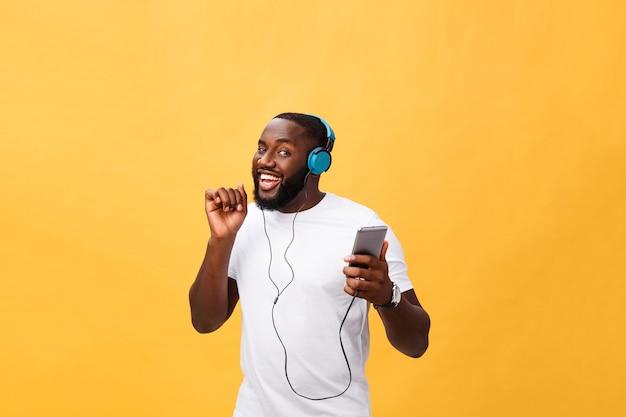 Homem afro-americano com fones de ouvido ouve e dança com música.