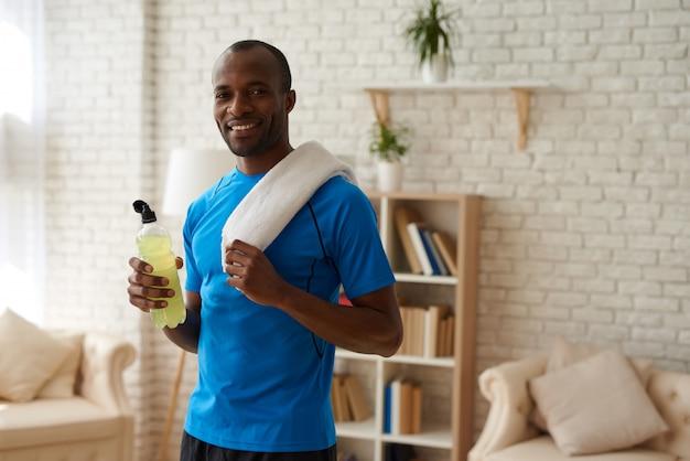 Homem afro-americano com garrafa é ter descanso.
