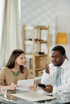Homem afro-americano com máquina de calcular, dando consultoria a uma jovem à mesa