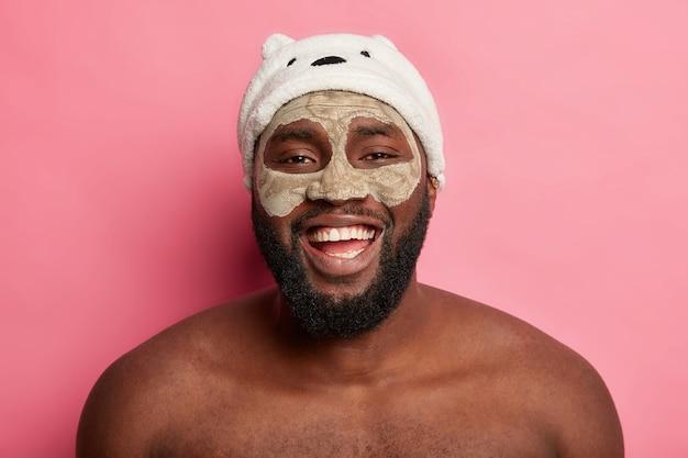 Homem afro-americano com máscara de argila, expressa emoções positivas isoladas