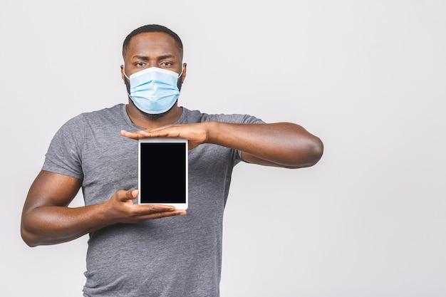 Homem afro-americano com máscara para protegê-lo do coronavirus. segurando a moldura de tela vazia do computador tablet.