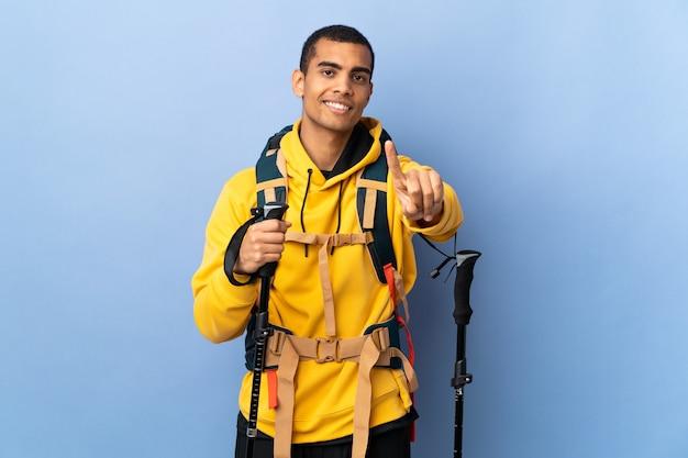 Homem afro-americano com mochila e bastões de trekking, mostrando e levantando um dedo