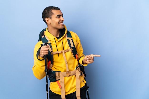 Homem afro-americano com mochila e bastões de trekking sobre fundo isolado apontando o dedo para o lado e apresentando um produto