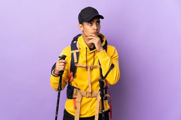 Homem afro-americano com mochila e bastões de trekking sobre fundo isolado, com dúvidas e expressão facial confusa