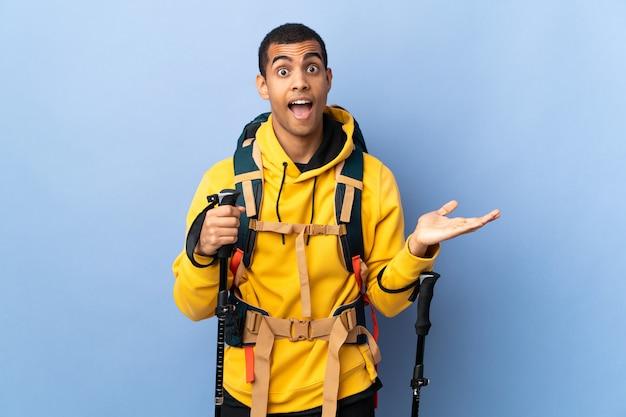 Homem afro-americano com mochila e bastões de trekking sobre fundo isolado com expressão facial chocada