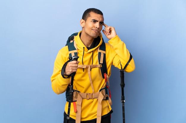 Homem afro-americano com mochila e bastões de trekking sobre fundo isolado fazendo o gesto de loucura colocando o dedo na cabeça