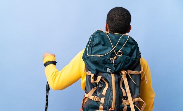 Homem afro-americano com mochila e bastões de trekking sobre fundo isolado na posição traseira