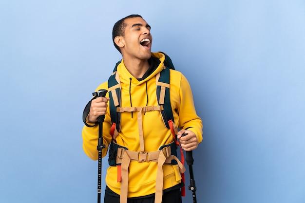 Homem afro-americano com mochila e bastões de trekking sobre fundo isolado rindo
