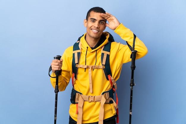 Homem afro-americano com mochila e bastões de trekking sobre fundo isolado saudando com a mão com expressão feliz