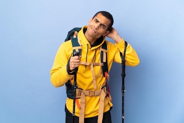 Homem afro-americano com mochila e bastões de trekking sobre fundo isolado, tendo dúvidas