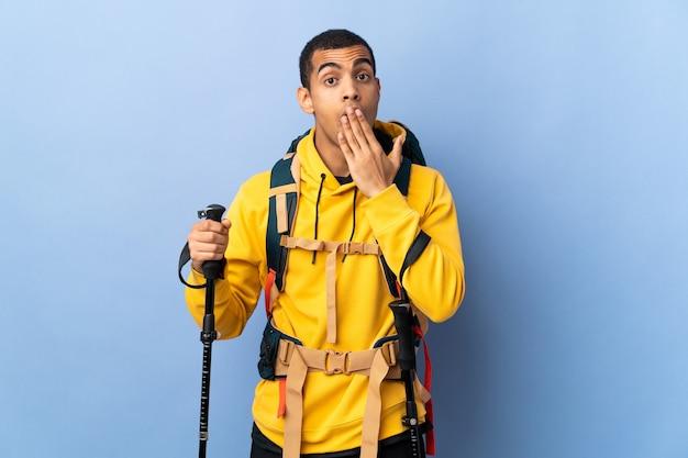 Homem afro-americano com mochila e bastões de trekking sobre um fundo isolado, bocejando e cobrindo a boca aberta com a mão