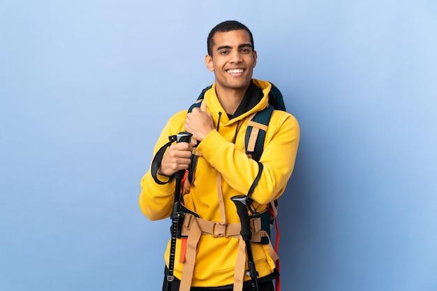 Homem afro-americano com mochila e bastões de trekking sobre um fundo isolado comemorando uma vitória