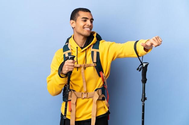Homem afro-americano com mochila e bastões de trekking sobre um fundo isolado fazendo um gesto de polegar para cima
