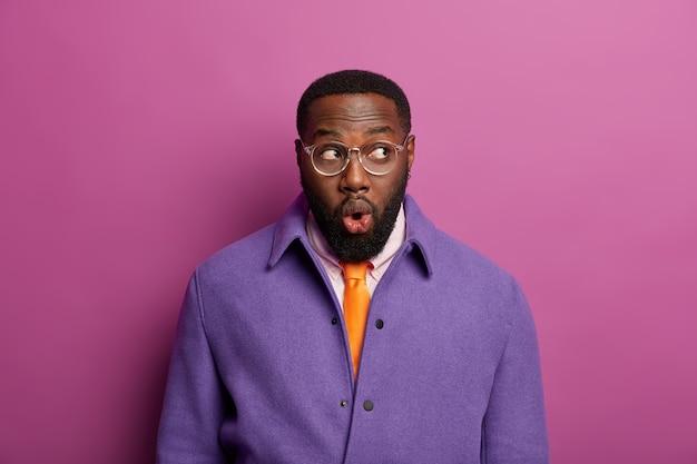 Homem afro-americano com olhos de inseto surpreso e pele escura, mantém os lábios arredondados, expressa choque após revelação inesperada, vestido com roupa formal. pessoas