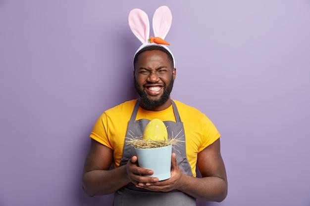 Homem afro-americano com orelhas de coelho segurando ovo de páscoa