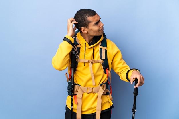 Homem afro-americano com pólos de mochila e trekking ao longo da parede isolada, tendo dúvidas enquanto coça a cabeça