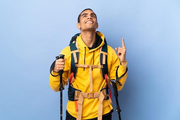 Homem afro-americano com pólos de mochila e trekking sobre parede isolada, apontando para cima e surpreso