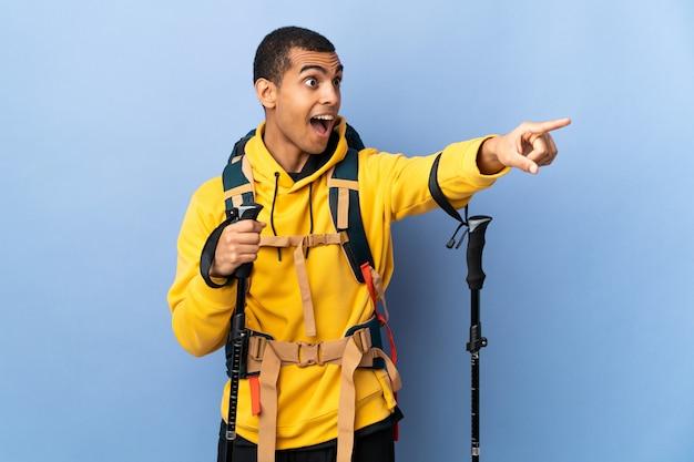 Homem afro-americano com pólos de mochila e trekking sobre parede isolada, apontando para fora
