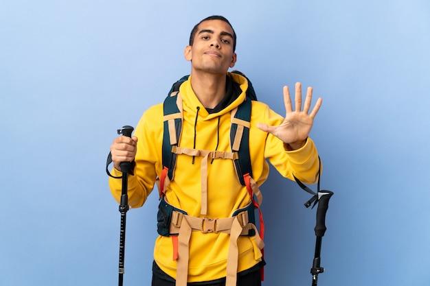 Homem afro-americano com pólos de mochila e trekking sobre parede isolada, contando cinco com os dedos