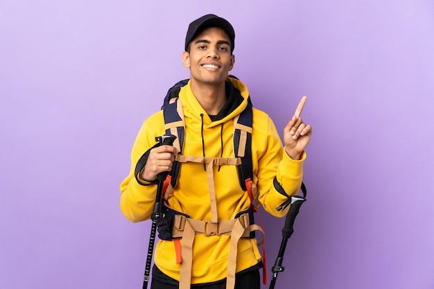 Homem afro-americano com pólos de mochila e trekking sobre parede isolada, mostrando e levantando um dedo em sinal dos melhores