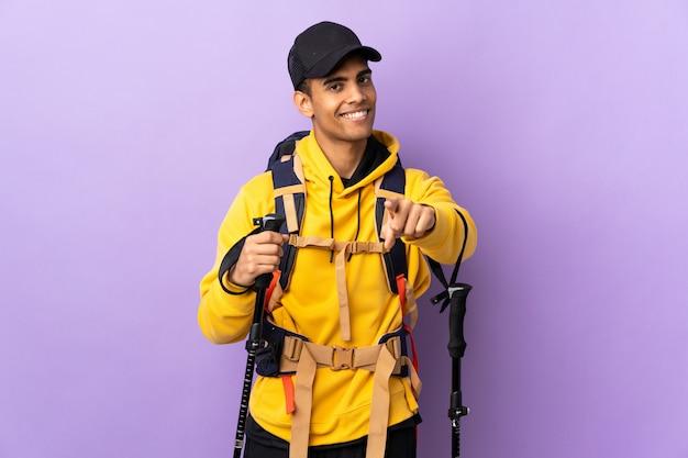 Homem afro-americano com pólos mochila e trekking sobre parede isolada, apontando a frente com expressão feliz