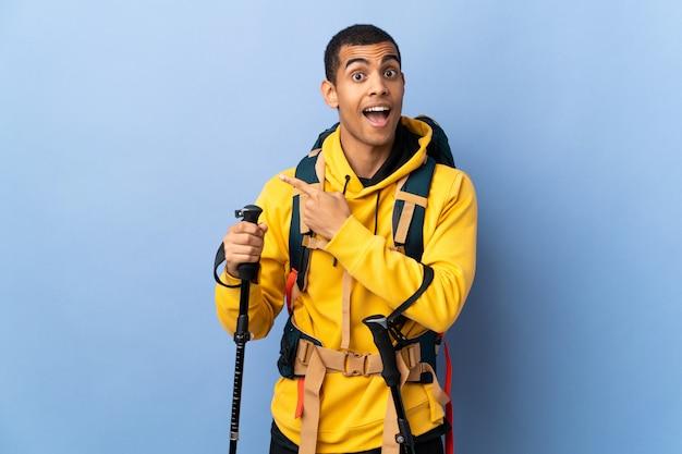 Homem afro-americano com polos mochila e trekking sobre parede isolada surpreendeu e apontando o lado