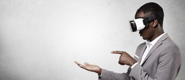 Homem afro-americano com roupa formal, usando fone de ouvido de realidade virtual 3d para telefone inteligente.