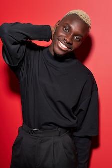 Homem afro-americano com sorriso cheio de roupas pretas, modelo de pele escura olha para a câmera, uma mão na parte de trás da cabeça, posando para a câmera isolada no espaço vermelho