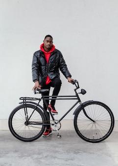Homem afro-americano com sua bicicleta na frente