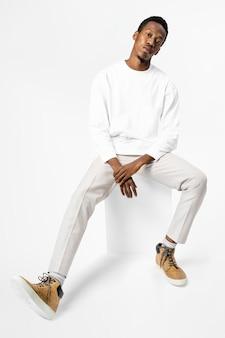 Homem afro-americano com suéter branco sentado em uma cadeira de corpo inteiro