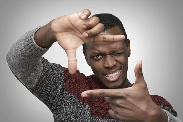 Homem afro-americano com suéter casual fazendo sinal quadrado com as mãos