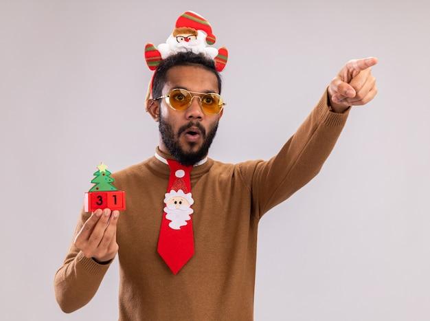 Homem afro-americano com suéter marrom e aro de papai noel