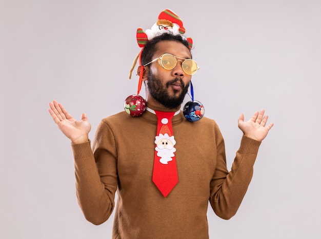 Homem afro-americano com suéter marrom e borda de papai noel na cabeça com gravata vermelha engraçada e bolas de natal nas orelhas parecendo confuso, levantando os braços em pé sobre um fundo branco