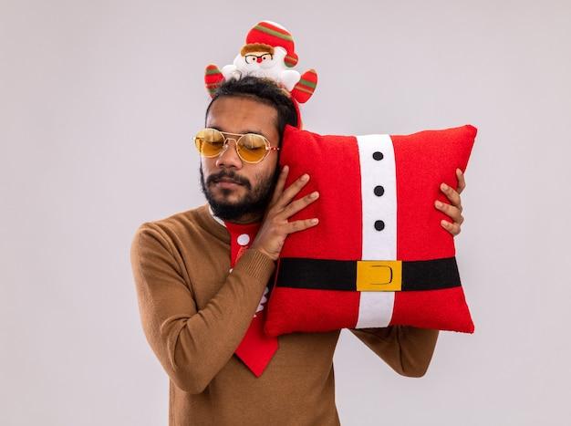Homem afro-americano com suéter marrom e borda de papai noel na cabeça com gravata vermelha engraçada segurando a almofada de natal, parecendo intrigado de pé sobre um fundo branco