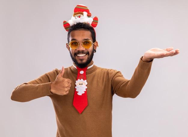 Homem afro-americano com suéter marrom e papai noel na cabeça com gravata vermelha engraçada mostrando os polegares para cima, apresentando com o braço sorrindo alegremente em pé sobre um fundo branco