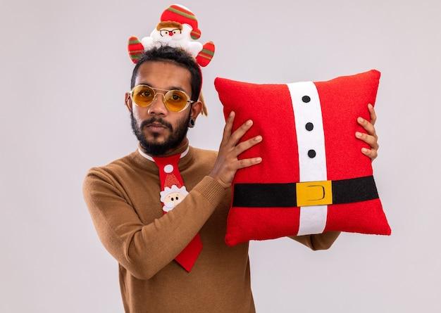 Homem afro-americano com suéter marrom e papai noel na cabeça com gravata vermelha engraçada segurando a almofada de natal, olhando para a câmera, sorrindo confiante em pé sobre um fundo branco