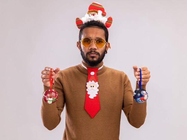 Homem afro-americano com suéter marrom e papai noel na cabeça com gravata vermelha engraçada segurando bolas de natal, olhando para a câmera com uma expressão triste em pé sobre um fundo branco