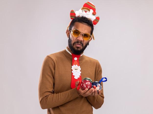 Homem afro-americano com suéter marrom e papai noel na cabeça com gravata vermelha engraçada segurando bolas de natal, olhando para a câmera, confuso e descontente em pé sobre um fundo branco