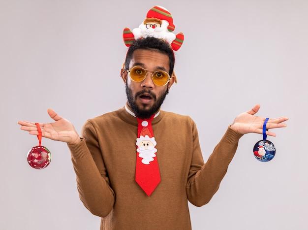 Homem afro-americano com suéter marrom e papai noel na cabeça com gravata vermelha engraçada segurando bolas de natal, olhando para a câmera confuso em pé sobre um fundo branco