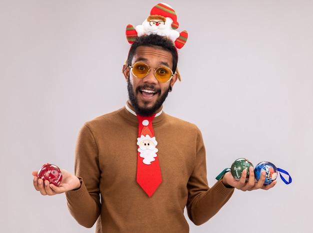 Homem afro-americano com suéter marrom e papai noel na cabeça com gravata vermelha engraçada segurando bolas de natal, olhando para a câmera, feliz e animado, em pé sobre um fundo branco