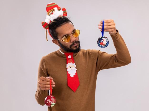 Homem afro-americano com suéter marrom e papai noel na cabeça com gravata vermelha engraçada segurando bolas de natal, parecendo confuso, tendo dúvidas em pé sobre um fundo branco