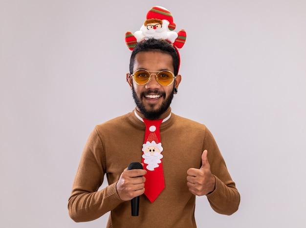 Homem afro-americano com suéter marrom e papai noel na cabeça com gravata vermelha engraçada segurando o microfone sorrindo e mostrando os polegares em pé sobre um fundo branco