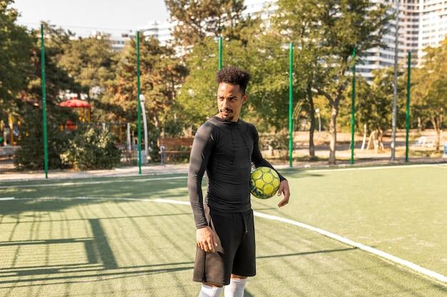 Homem afro-americano com tiro certeiro posando com uma bola de futebol