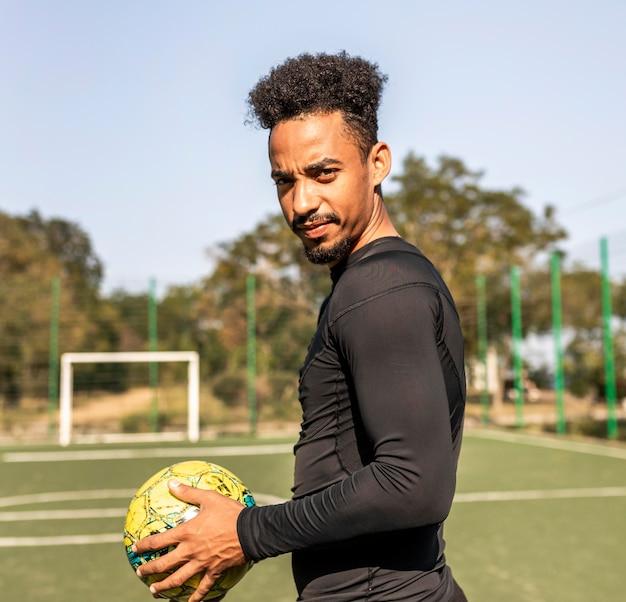 Homem afro-americano com tiro médio posando com uma bola de futebol