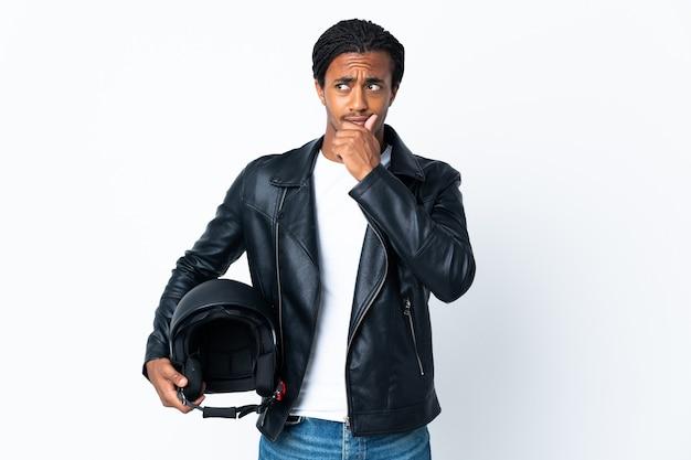 Homem afro-americano com tranças, segurando um capacete de motociclista isolado no branco, tendo dúvidas e pensando