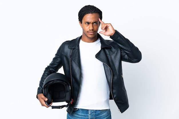 Homem afro-americano com tranças, segurando um capacete de motociclista, isolado no fundo branco, tendo dúvidas e pensando