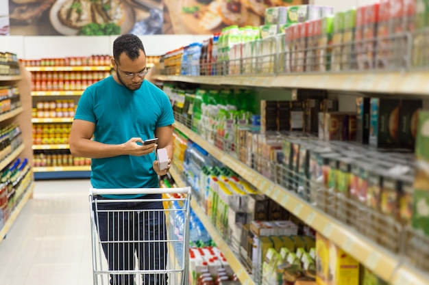 Homem afro-americano concentrado lendo a lista de compras em smartphone