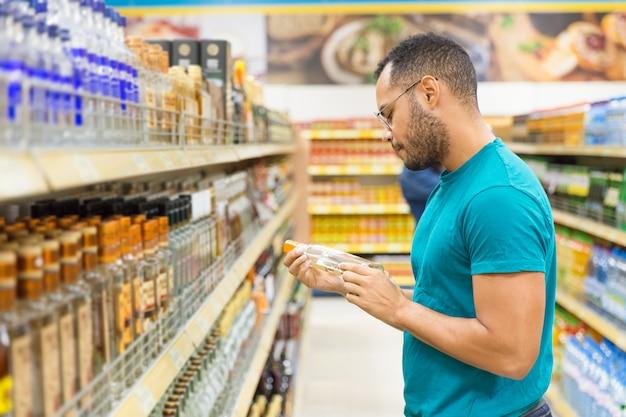 Homem afro-americano concentrado segurando bebida alcoólica