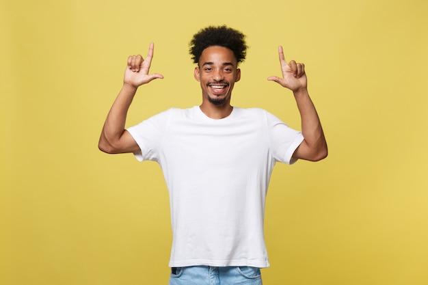 Homem afro-americano considerável novo sobre o fundo amarelo que aponta para cima.