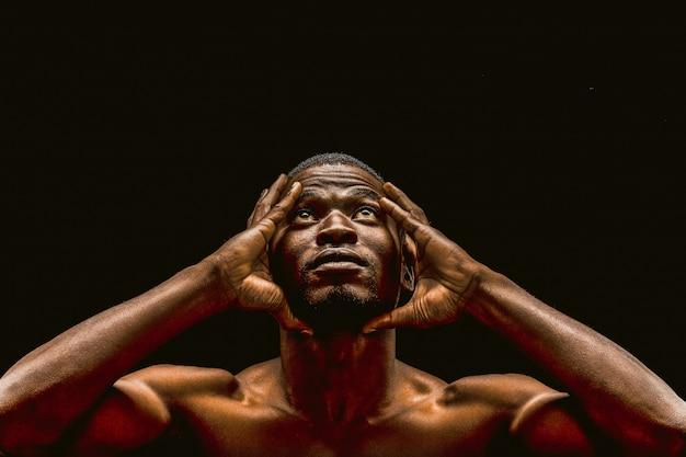 Homem afro-americano considerável que olha acima de tocar nas mãos da cabeça, retrato do atleta de pele escura nu isolado no fundo preto.